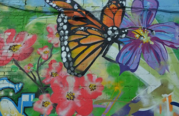 a monarch butterfly in a mural along with many pink and purple flowers