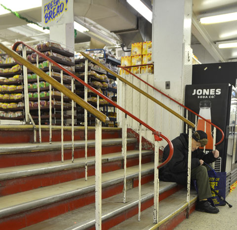 interior of Honest Eds store as it gets ready to close down. an old man with a cane sits on the steps between two sections of the store