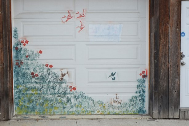 stencil art on a white garage door. greenery, a hummingbird, three swallows in flight, a deer, some red flowers