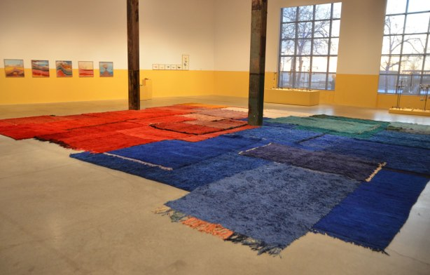 main exhibit room of The Power Plant Contemporary Art Gallery, large room with two large windows in which the low afternoon sun is shining. Exhibit by Yto Barrada consisting of red, green and blue carpets on the floor. some framed pictures on the far wall, walls have been painted yellow up to about 4 feet from the floor.