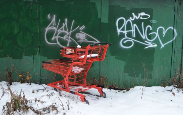 a bright red shopping cart has been abandoned in front of a green garage door in a snowy alley
