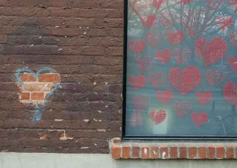 pink hearts on a cyan coloured window beside a heart on a brick wall graffiti