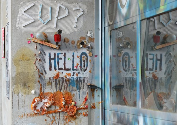 a small collection of little things on a wall including the word sup? made with white strips of wood. Also the word hello is painted on the wall. Collage includes a large spring, a light bulb and blobs of something orange.