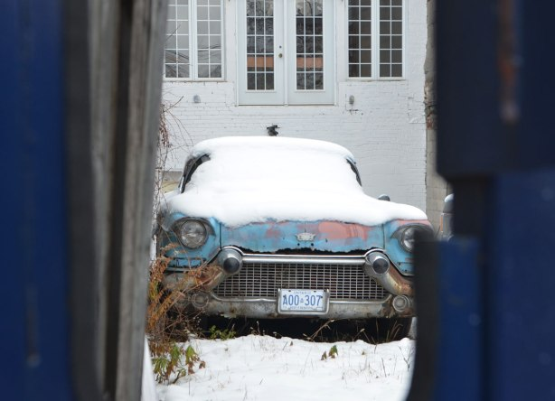 looking through a hole in a blue fence, an old light blue car is parked in a backyard, covered with snow, the white of the house is behind the car.