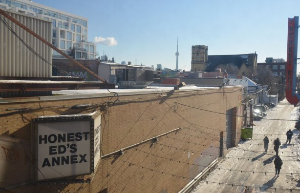looking down at an icy alley where four people are walking between buildings, sign on building says Honest Eds Annex,