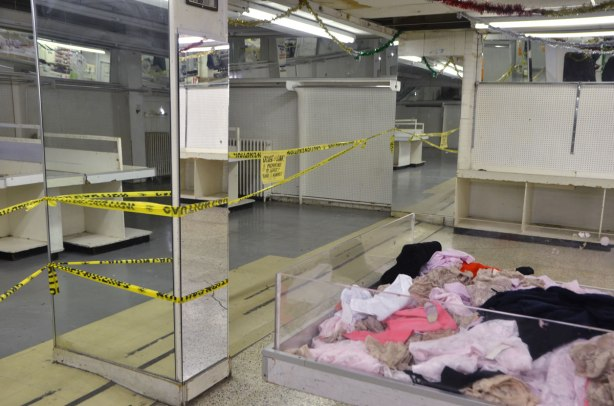 interior of Honest Eds store as it gets ready to close down. ladies underwear in a bin for sale, surrounded by empty bins and wall space, lots of mirrors. Yellow caution tape marks off a section of the store that is now closed.