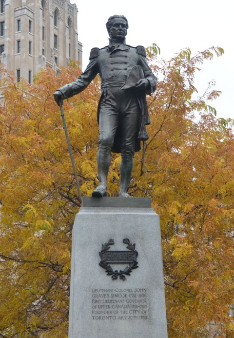 statue of a man in bronze standing on a grey stone column, yellow tree behind him. He's got a sword in one hand, with its point on the ground and he is leaning on it slightly