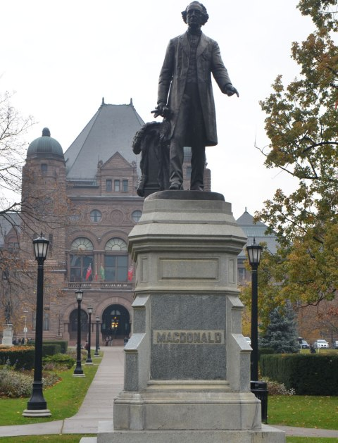 statue of Sir John A. Macdonald, first Prime Minister of Canada, on a grey day, in front of the Ontario Legislature at Queens Park in Toronto,