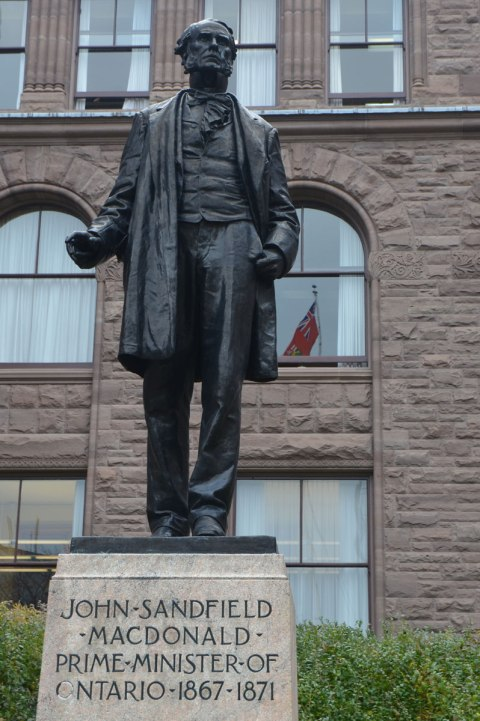 statue of a man, John Sandfield Macdonald, in front of the parliament buildings at Queens Park. An Ontario flag is reflected in the windows of the building.