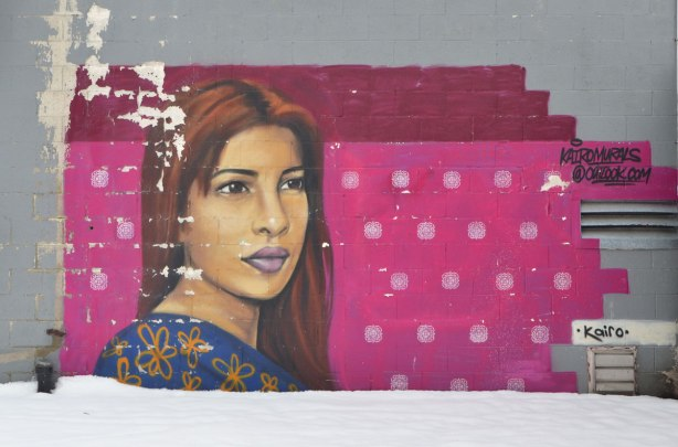 mural of a woman's head by kairo. Background has been painted a dark pink, with white spots. WOman has long reddish brown hair.