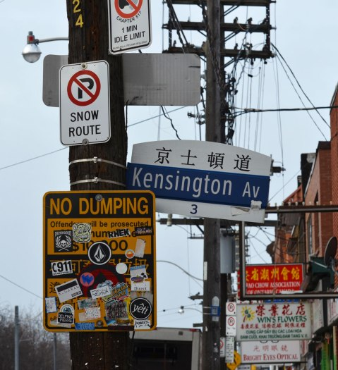 two hysro poles, one with a lot of signs on it and the other with three horizontal wood sections at the top of it. Signs are a street sign for Kensington Ave in both English and Chinese, a yellow no dumping sign that has been covered in stickers, and a no parking sign. Signs for Chinese businesses are in the background.
