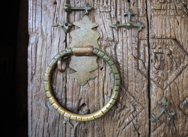 an old brass knocker on an old wood door