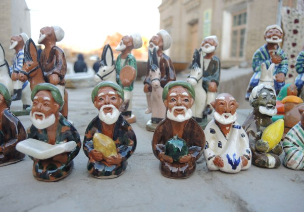 a line of little ceramic figurines that are for sale at an outdoor vendor, old men with white beards and green hats