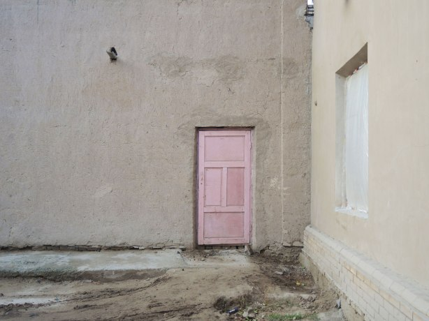 a pale pink door on a building with no windows