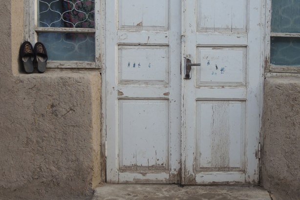 closed white double doors with small windows on either side, a pair of shoes neatly sitting by the window.