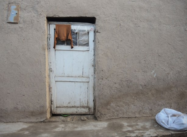 a brown sweater is hanging over the top of an old white door on a mud and straw house