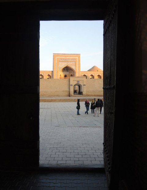 view through a doorway to a courtyard in front of a mosque, with a group of people standing there