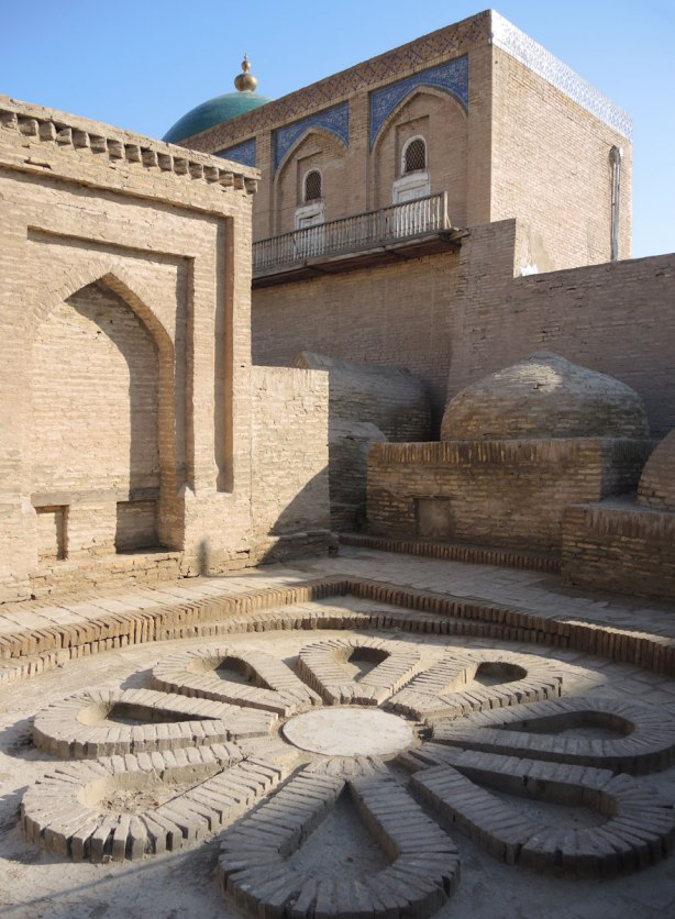 brick buildings with blue dome, and sunflower shaped brick design on the ground, Khiva