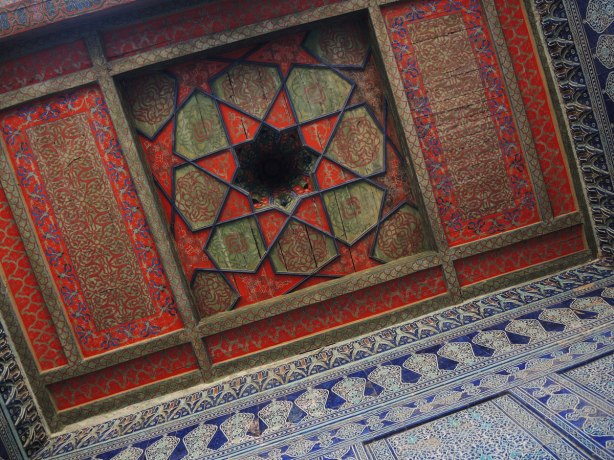 painted wood ceiling in an old building in Khiva, the harem of the castle, in red and green, octagonal pattern, some of the walls are also showing, they are covered in blue and white tile