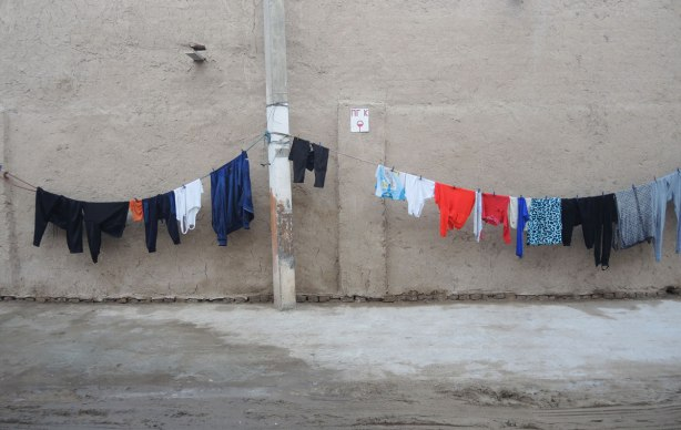 a long line of laundry hangs in front of an old brick wall