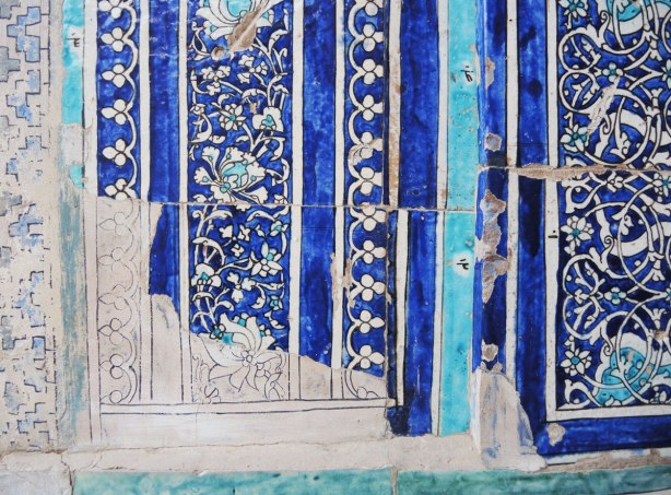 broken tile mosaics in blues and white, drawing on the wall to show where the missing tiles would go