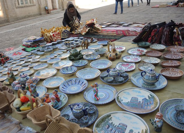 a woman inspects a plate, many plates for sale, on a mat on the ground, all ceramic, some blue and white and some with pomegranate patterns on them.
