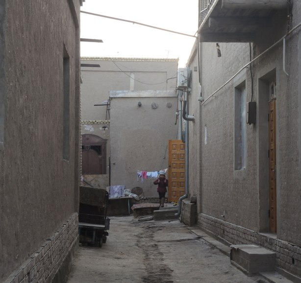 a girl comes out of a doorway at the end of a lane, morning, about to go to school. sand coloured houses on either side, laundry hanging at the end of the alley