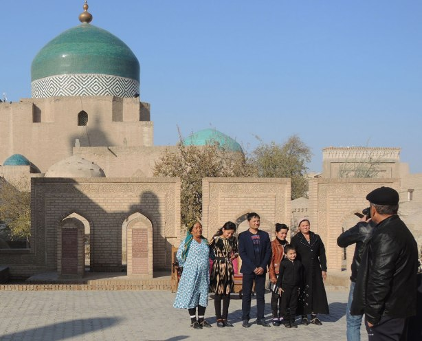 local Uzbeks (probably) lining up in front an old brick building with a blue dome to have their picture taken