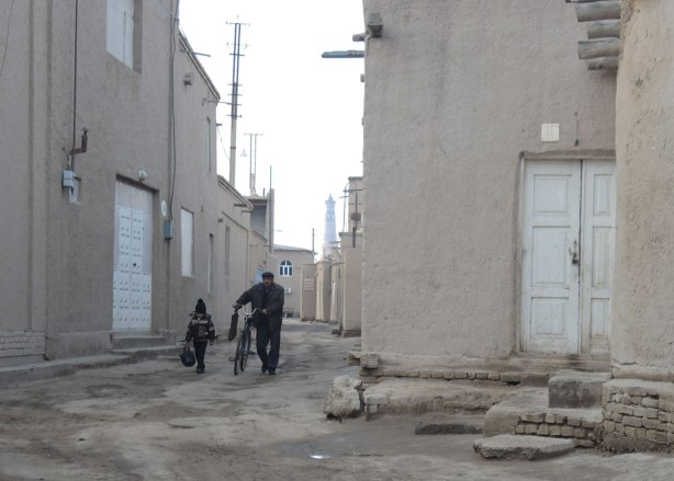 a man walks his bike while a gilr walks beside him carrying her scholl bags, morning, in an alley in khiva