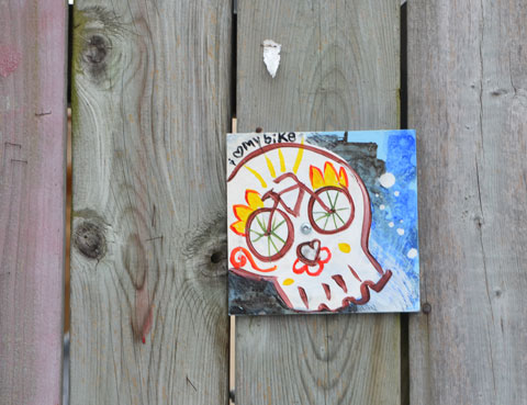 a small painting that has been hung a fence. A white skull with the eyes drawn as the wheels of a bike. The words say I love my bike, with the word love being a small heart.