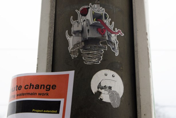 two stickers on a pole. The top one is a lovebot grominator joint venture hybrid character with a very long red tongue. The other is a little round faced guy with his tongue sticking out.