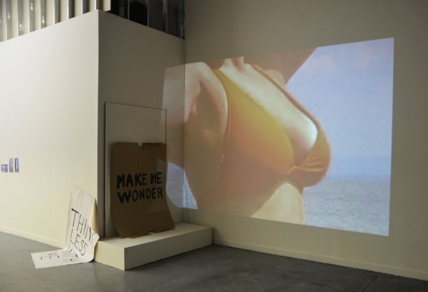 walls of a n art gallery with some of the work of Oscar Figueroa. A projection of a woman's chest in a bikini top, a piece of brown cardboard with the words 'Make me wonder' and a piece of paper, large white paper, half on the floor and half propped up on the wall that says