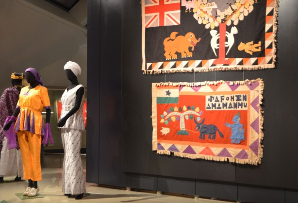 two flags displayed on a black background, with three femail mannequins dressed in traditional Ghanese costume.