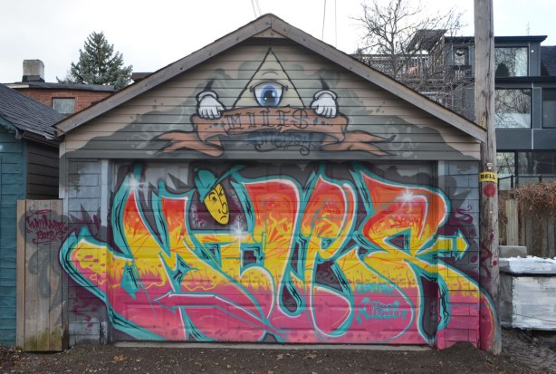 street artist miles tag and colourful street art on a garage door