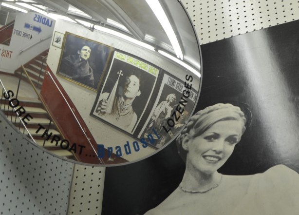 interior of Honest Eds store as it gets ready to close down. a black and white photo of a young woman on a wall beside a convex mirror showing the stairwell. also an ad printed right on the mirror for bradasol lozenges