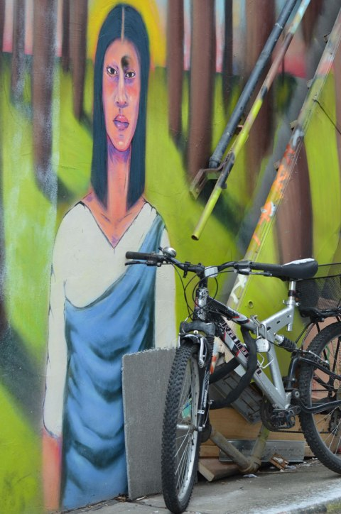 part of a mural in a Kensington lane of a woman with long dark hair and a white and blue dress, she is standing. In front of her is parked a bike.
