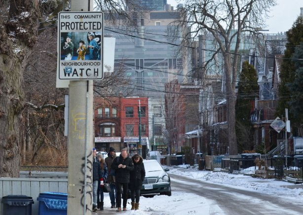 looking down a street in Kensington, looking towards Spadina, older brick housses on the street, a group of people walking down the sidewalk, snow on the ground, winter trees, a neighbourhood watch sign that has been altered with a picture of the three boys from the movie 3 Ninjas.