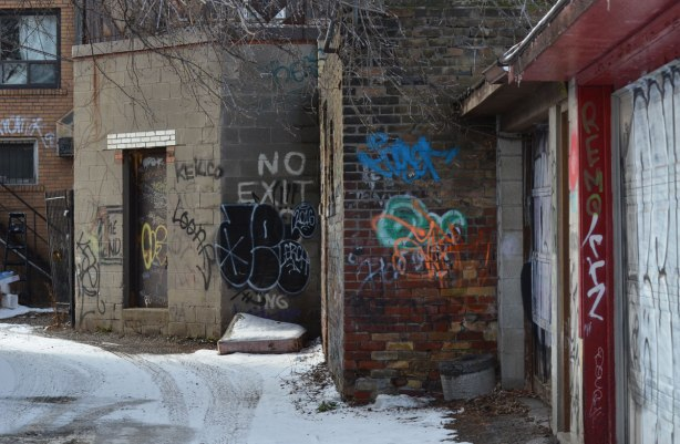 the end of a dead end alley, with graffiti on one of the walls, and a sign that says no exit painted on the wall in white.