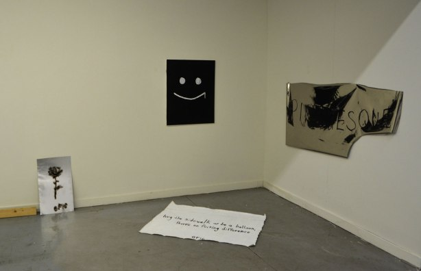 4 pieces of art in a gallery. a white happy face on black paper, a shiny piece of paper with a corner ripped off with the word picturesque written on it.
