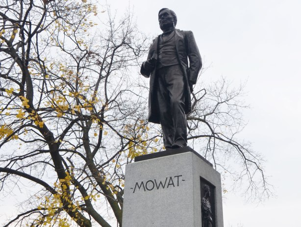 black statue of a man, Sir Oliver Mowat, standing with a book in one hand, and the other hand behind his back. The figure is on top of a grey stone rectangular column, autumn tree in the background.