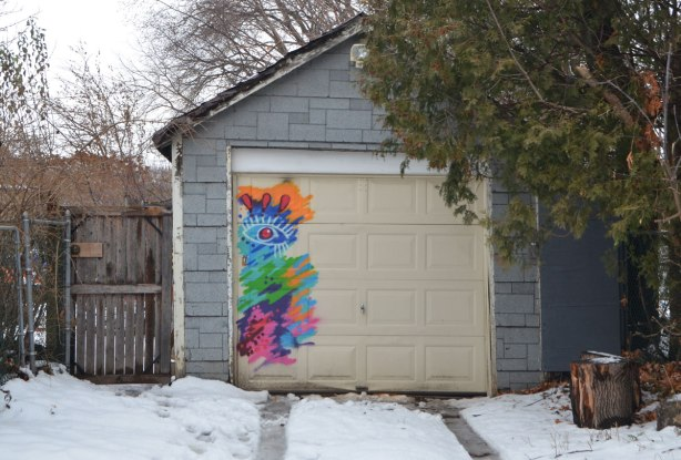 An old single car garage with grey shingle material covering it. Yellowish beige garage door with a small brightly coloured street art piece on it that includes an eye