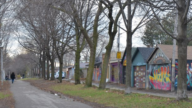 a lane running parallel to a park with garages on the other side, a line of large trees by the garages. Most of the garage doors are covered with street art