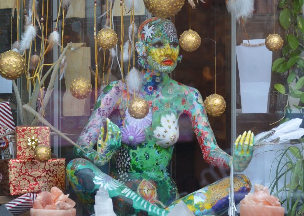 mannequin in a window sitting in a yoga position, and covered in painted patterns, multicoloured, gold Christmas balls are hanging from the ceiling around her.