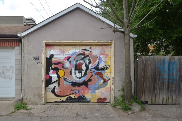 abstract street art on a garage door in a lane, by Pascal Paquette, swirls of colour