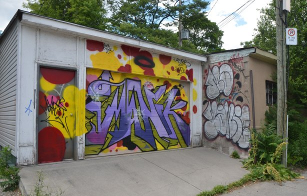street art on a garage door in a lane, purple text graffiti with red and yellow background, colourful, abstract