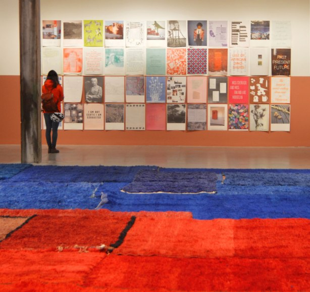 Part of an exhibit by Yto Barrada of a series of posters printed on paper and loosely tacked to the wall, of images and words. They are arranged in a grid of 12 x 8 pictures. A woman is standing in front of them, reading the words on one. Blue and red carpets are on the floor in the foreground.