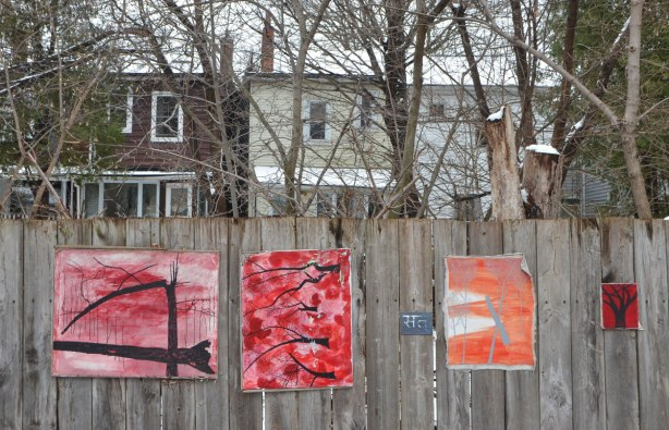 small amateur paintings displayed on a wood fence, with trees and houses in the background, snowy day, Craven Road in Toronto, two paintings of black trees (no leaves) on red, and one grey tree on orange background,