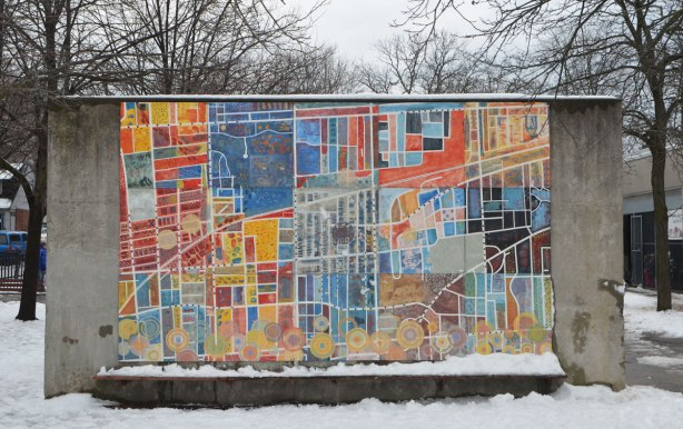 a mural on a conrete wall in a schoolyard that is a map of the area with the school in the center, colourful, about 8 feet high and twelve feet wide.