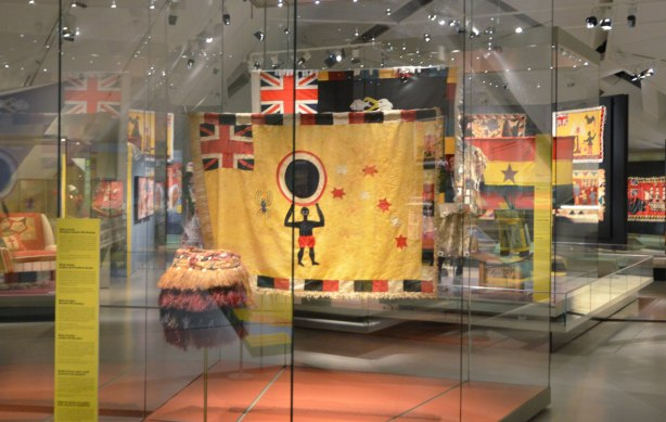 museum exhibit of asafo flags from Ghana, colourful flags of militia groups in yellows, reds and black. Many are hanging in display cases.
