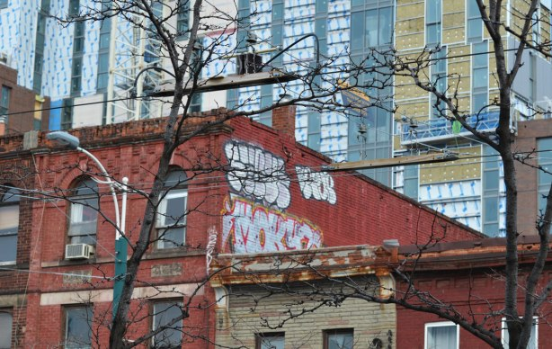 graffiti on the top of a red brick building, trees in front, a large new condo being built behind.